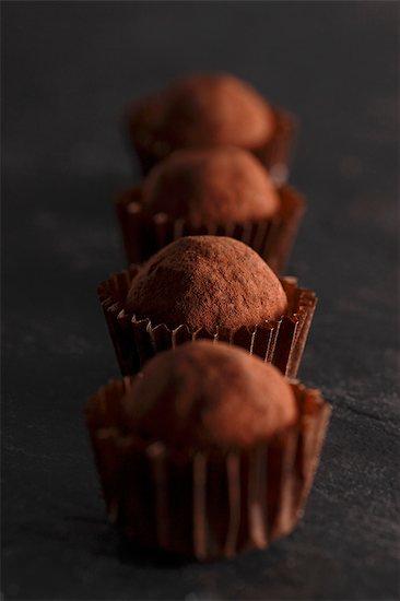 A row of chocolate truffle pralines Stock Photo - Premium Royalty-Free, Image code: 659-06670960