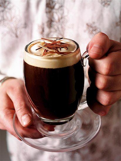 Hands holding a glass mug of Irish coffee Stock Photo - Premium Royalty-Free, Image code: 659-06903364