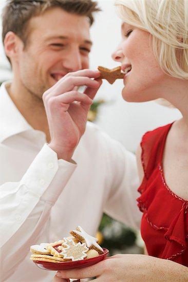 Man feeding Christmas biscuit to woman Stock Photo - Premium Royalty-Free, Image code: 659-03526688