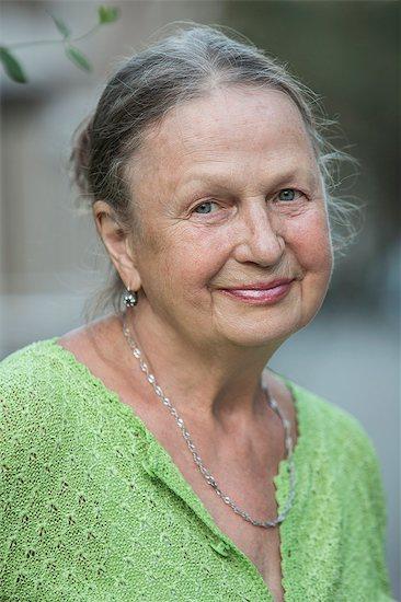 Close-up portrait of senior woman smiling outdoors Stock Photo - Premium Royalty-Free, Image code: 653-07761593