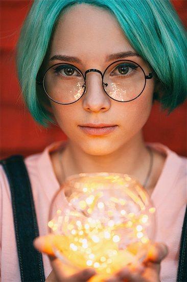 Teenage girl wearing eyeglasses holding illuminated string lights Stock Photo - Premium Royalty-Free, Image code: 653-09037352