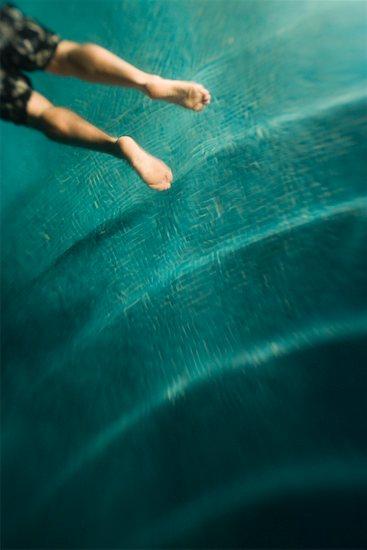 Legs of man swimming underwater Stock Photo - Premium Royalty-Free, Image code: 673-02140917