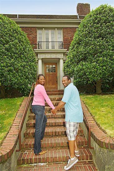African couple walking towards house Stock Photo - Premium Royalty-Free, Image code: 673-02143167
