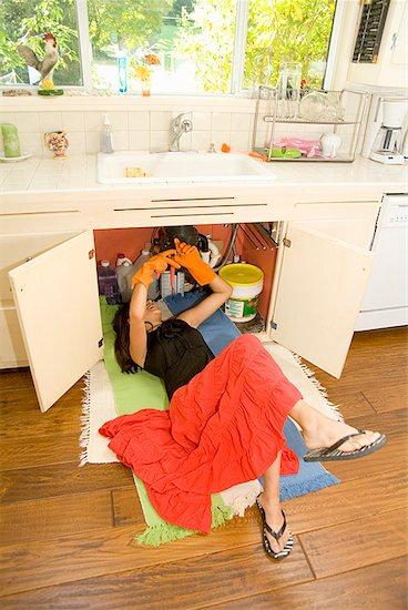 Woman fixing plumbing under sink Stock Photo - Premium Royalty-Free, Image code: 673-02143456