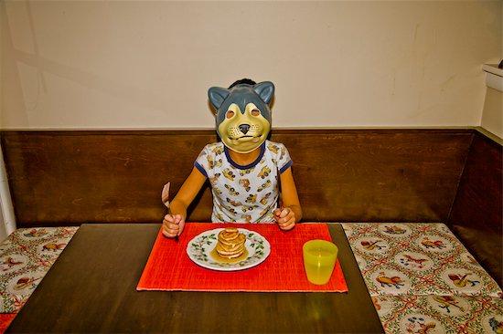 boy wearing dog mask at table Stock Photo - Premium Royalty-Free, Image code: 673-03826556
