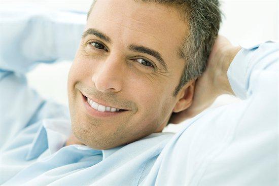 Man smiling at camera, hands behind head, portrait Stock Photo - Premium Royalty-Free, Image code: 695-03390332