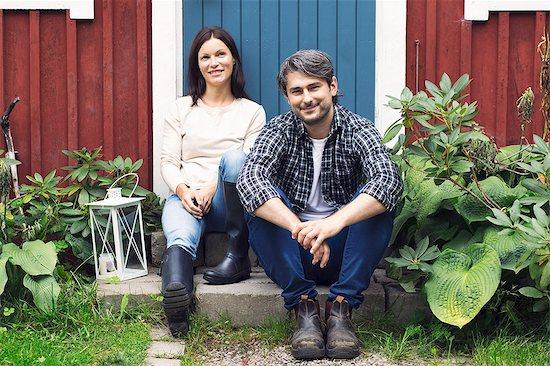 Portrait of smiling mid adult couple sitting outside farmhouse Stock Photo - Premium Royalty-Free, Image code: 698-08007935