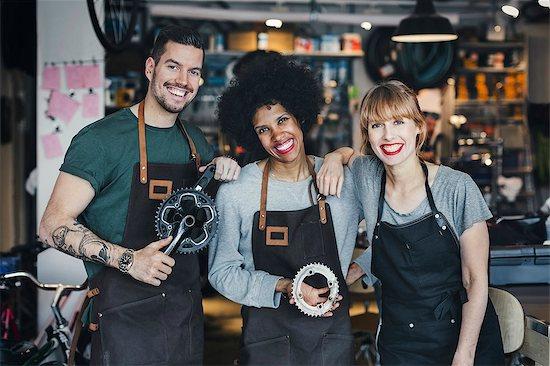 Portrait of happy multi-ethnic mechanics with gears in workshop Stock Photo - Premium Royalty-Free, Image code: 698-08226415