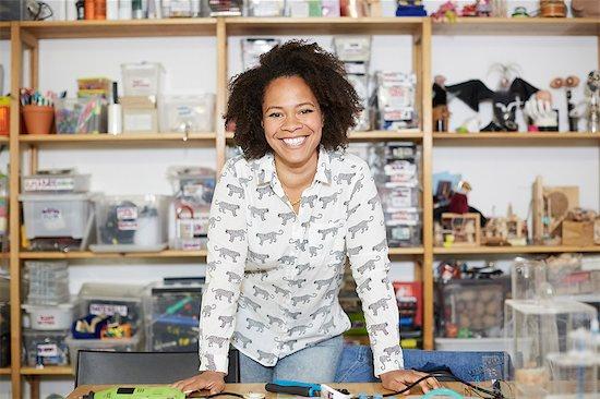 Portrait of confident female technician standing against shelf at workshop Stock Photo - Premium Royalty-Free, Image code: 698-09054500