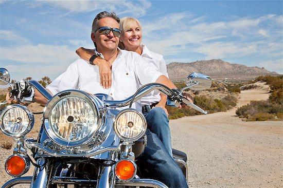 Senior couple on desert road sitting on motorcycle Stock Photo - Premium Royalty-Free, Image code: 693-06667815