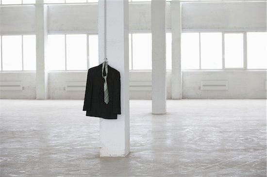 Suit jacket hangs on pillar in empty warehouse Stock Photo - Premium Royalty-Free, Image code: 693-03474202