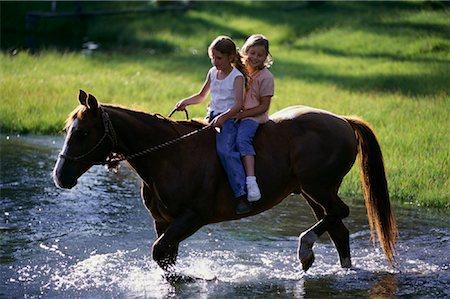 Two Girls Riding Horseback Through Stream Stock Photo