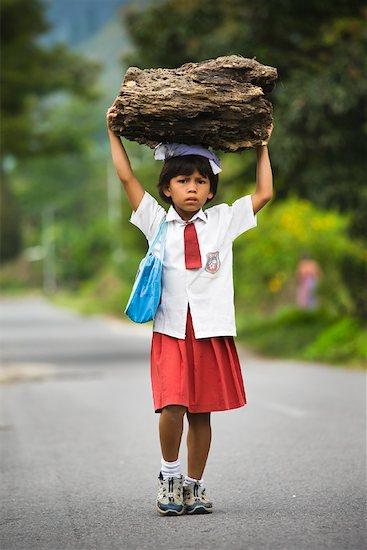 Schoolgirl Carrying Wood, Ambarita, Samosir Island, Sumatra, Indonesia Stock Photo - Premium Rights-Managed, Artist: R. Ian Lloyd, Image code: 700-02046559